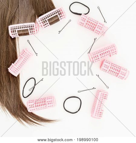 Hairs and woman's curlers, stylish beauty concept on white background. Flat lay. Top view.