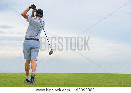 Golf player hitting shot with club on course, Man playing golf on beautiful sunny green golf course. Hitting golf ball down the fairway from the tee