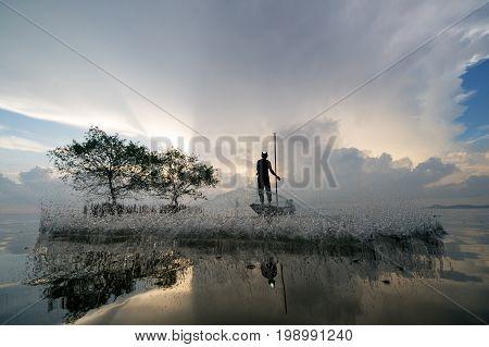 Fisherman throwing fishing net during sunrise in Pak Pra Village, Phatthalung, Thailand
