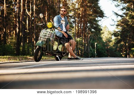 Image of concentrated young bearded man standing near scooter outdoors. Looking aside.