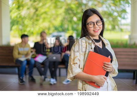 Education first Beautiful female college student holding her books smiling happily standing in an auditorium people education learning high school program smart teenager concept copy space