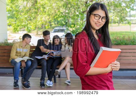 Education first, Beautiful female college student holding her books smiling happily standing in an auditorium people education learning high school program smart teenager concept copy space