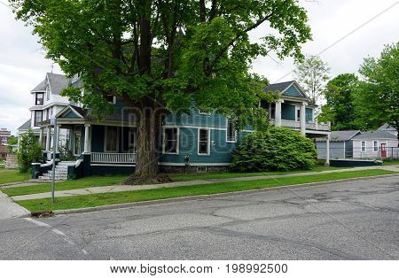 CADILLAC, MICHIGAN / UNITED STATES - MAY 31, 2017: A large elegant blue Victorian mansion, with a wraparound porch, a balcony, and a maple shade tree, in Cadillac's Courthouse Hill Historic District.