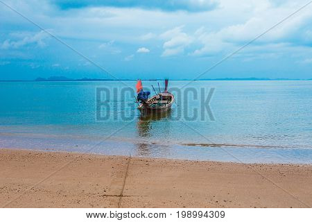 Fishing boat with a coracle boat stored on deck. Close-up of colorful blue boat with red trim. Reflection in water. Fishing is an important industry