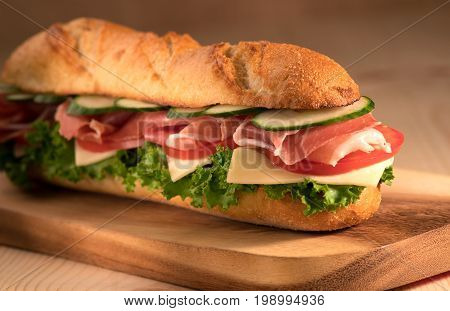Fresh crispy sandwich with prosciutto cheese tomatoes lettuce cucumbers on a wooden background.Close Up. Healthy concept.