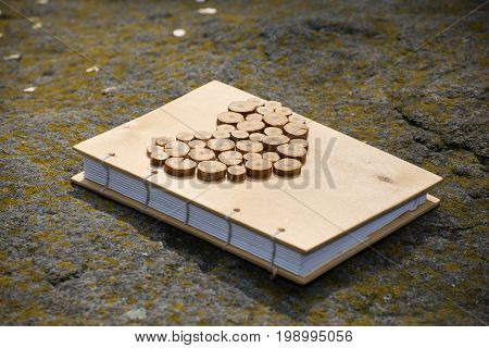 A closed diary with a wooden cover and heart lies on the stones