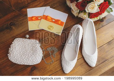 Wedding shoes and bouquet of red and white roses on wooden background marriage concept