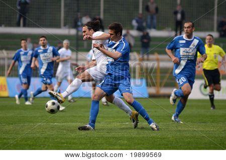 KAPOSVAR, HUNGARY - APRIL 16: Lorant Olah (in white) in action at a Hungarian National Championship soccer game - Kaposvar vs MTK Budapest on April 16, 2011 in Kaposvar, Hungary.