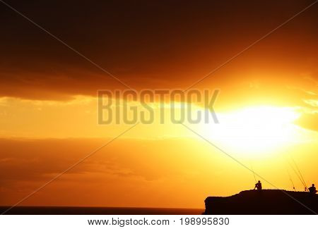 Bali, Indonesia - 23 June 2012   Sunset of Kuta Beach with Silhouettes of People Fishing in a Big Coral