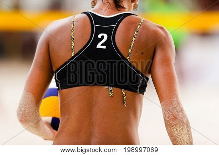 Volleyball beach player serving is a female beach volleyball player getting ready to serve the ball.