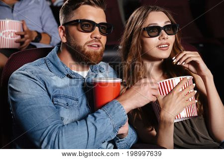 Image of concentrated friends loving couple sitting in cinema watch film eating popcorn and drinking aerated sweet water.