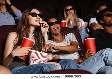 Picture of cheerful friends sitting in cinema watch film eating popcorn and drinking aerated sweet water.