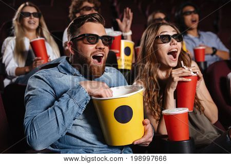 Image of laughing friends sitting in cinema watch film eating popcorn and drinking aerated sweet water.