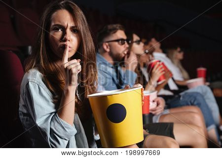 Picture of young lady sitting in cinema watch film and eating popcorn showing silence gesture.