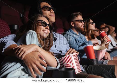 Image of young loving couple sitting in cinema watch film and hugging