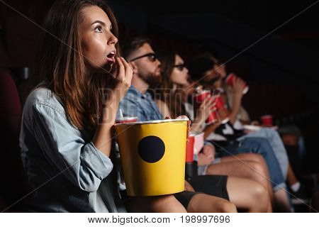 Image of young lady sitting in cinema watch film and eating popcorn.