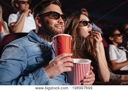 Image of loving couple friends sitting in cinema watch film eating popcorn and drinking aerated sweet water.