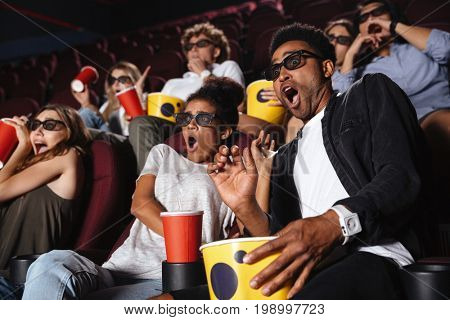 Picture of scared young friends sitting in cinema watch film drinking aerated sweet water.