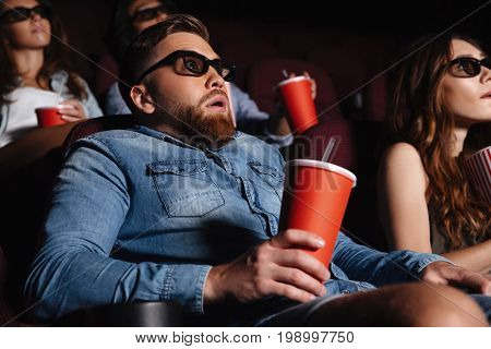 Image of shocked young man sitting in cinema watch film drinking aerated sweet water.
