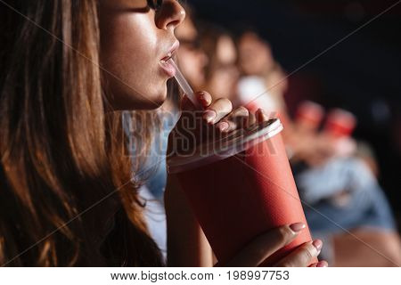 Cropped picture of young lady sitting in cinema watch film drinking aerated sweet water.