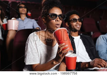 Image of serious young friends sitting in cinema watch film drinking aerated sweet water.