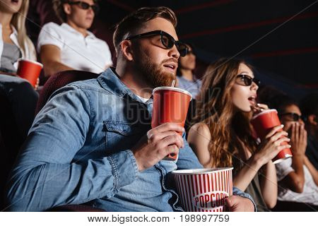 Picture of concentrated loving couple friends sitting in cinema watch film eating popcorn and drinking aerated sweet water.