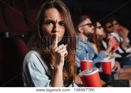 Picture of young lady sitting in cinema watch film and showing silence gesture.