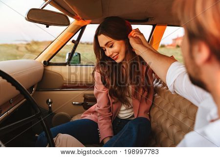 Young man flirting with his smiling girlfriend by touching her hair and holding her hand while sitting inside a retro car