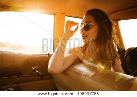 Beautiful young woman in sunglasses sitting on a front seat inside a car and looking backwards