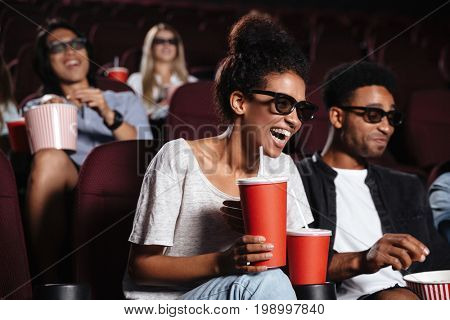 Picture of happy young friends sitting in cinema watch film drinking aerated sweet water.
