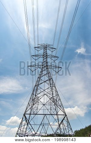 High voltage transmission towers Background sky blue - Green grass THAILAND