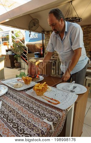 SIDE TURKEY - JULY 07 2015: The restaurant in Side the waiter served the meat from the clay pot.