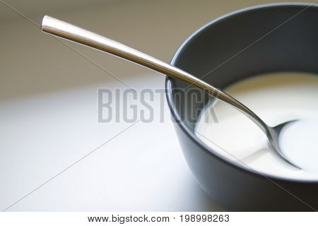 A plate of milk and a spoon close up on white table. Breakfast at home, abstract background.