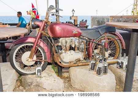 SIDE TURKEY - JULY 07 2015: Old bike and empty bottles of whiskey in front of the restaurant at the waterfront. Anatolian coast - a popular holiday destination in summer of European citizens.