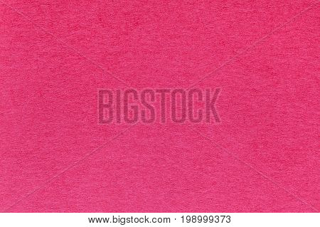 Texture of old bright red paper background closeup. Structure of dense kraft magenta cardboard.