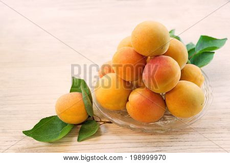 Fresh apricot. Ripe apricots with leaves on a glass plate. Wooden background. Top view. Copy space