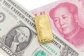Gold bar over the US dollar bill and Chinese yuan banknote on white background economy finance concept. poster