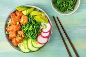 An overhead photo of poke, traditional Hawaiian raw fish salad, with a plate of wakame, sea vegetable, with chopsticks and copy space. Selective focus poster