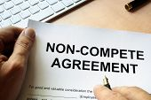 Man is signing Non compete agreement. Outsourcing concept. poster