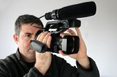 Professional cameraman (age 40) filming footage with video camera with attached microphone. Real people. Copy space poster