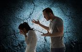people, relationship difficulties, conflict and family concept - angry man abusing woman over cracked concrete background poster