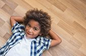 Playful little boy with curly hair lying on wooden floor and think. Top view of shy african kid looking at camera with copy space. Pensive black boy lying at the floor with hands behind the head. poster