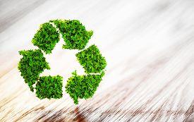 Fresh Green Leaf Recycle Symbol On Wooden Desk With Blurred Background. 3D Illustration.