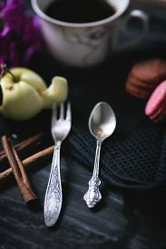 Vintage coffee spoon and fruit fork. Cinnamon, coffee and macaroni on the old table.