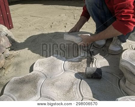 A Male Worker Holds A Concrete Pavement Tile And A Rubber Mallet Lies Nearby. The Concept Of Work On