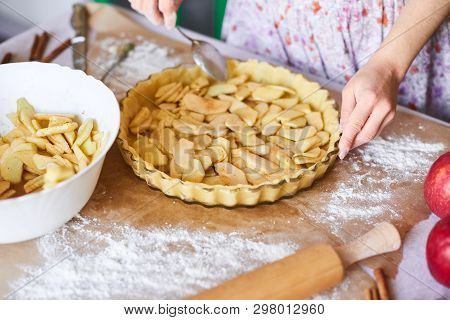 Woman Adds Sliced Apples To Apple Pie. Woman Hands Working A Pie Dough In A Tray, On A Kitchen Table
