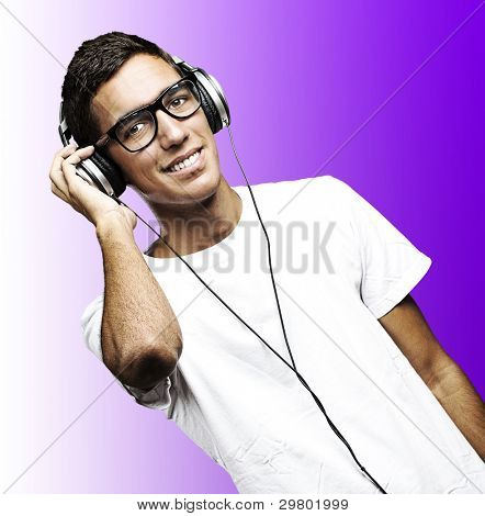 portrait of young man with glasses and headphones listening to music on a purple background