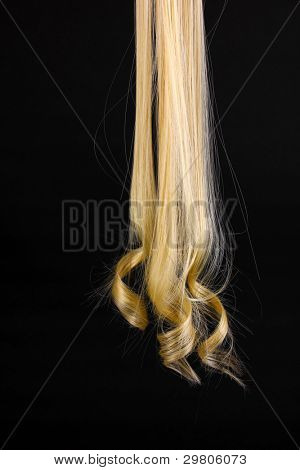 Curly blond hair isolated on black