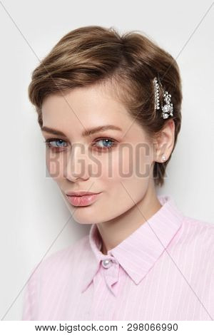 Vintage style portrait of young beautiful woman with fancy hairpins in her hair