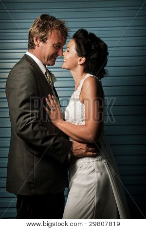 Bride And Groom Touching Noses Against A Blue Wall